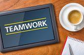 A tablet on a wooden desk - Teamwork