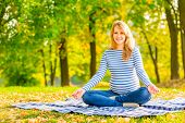 Cheerful Pregnant Woman In The Park Sitting In The Lotus Position
