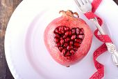 Pomegranate seeds in the form of heart on a wooden background.