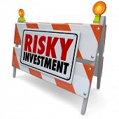 Risky Investment words on a barrier or road construction warning sign to illustrate the need for caution in a dangerous investing strategy for money growth
