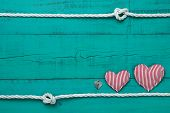 Blank blue wooden sign with hearts and lock with white rope border with knots