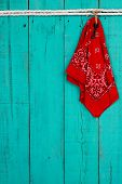 Red bandana and key hanging by rope on antique teal blue background