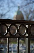 Decorative Details Of Metal Fence With A Silhouette Of A Dome In The Background