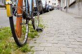 picture of paved road  - Close detail of a bike parked on a paving road - JPG