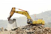 stock photo of track-hoe  - A large trackhoe or tracked excavator moving rock from a hill at an airport runway expansion project - JPG
