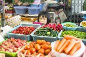 BANGKOK, THAILAND - DEC 15, 2014: Unidentified girl child seller on the Burmese street market in Bangkok. There is 16,000 registered street vendors in Bangkok.