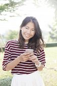 Portrait Of Beautiful Young Woman And Smart Phone In Hand Smiling To Camera Use For Modern Activitie
