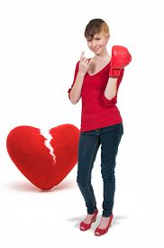 picture of heartbreaking  - Beautiful woman in wearing a boxing glove in front of a broken heart  - JPG