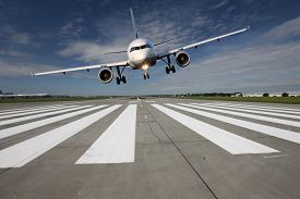 image of aeroplan  - Landing aircraft low over the runway with stretched landing gear - JPG