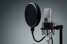 picture of studio  - Studio microphone and pop shield on mic stand against gray background - JPG