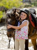 stock photo of horse girl  - sweet beautiful young girl 7 or 8 years old hugging head of little pony horse smiling happy wearing safety jockey helmet posing outdoors on countryside in summer holiday - JPG