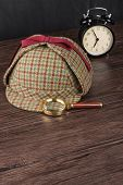 image of private investigator  - Deerstalker  hat and magnifying glass on Old Wooden table - JPG