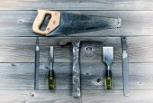 image of chisel  - Vintage concept of used tools on rustic wooden boards consisting of hammer metal files hand saw and chisels - JPG