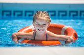 stock photo of lifeline  - happy cute little girl swims with a lifeline in the pool in  summer - JPG