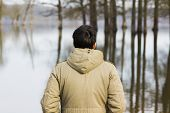 pic of observed  - Man in jacket observing the river from the shore in Lonjsko polje - JPG