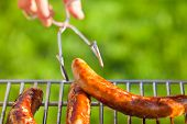 picture of tong  - Hand hold tongs for food with at barbecue grill - JPG
