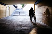 picture of underpass  - A woman pushing her bike in an underpass - JPG