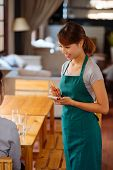 picture of apron  - Pretty female waiter in apron taking an order - JPG