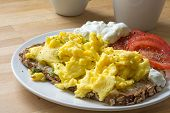 picture of scrambled eggs  - scrambled eggs on rustic bread with tomatoes and curd cheese cream - JPG