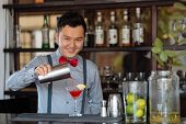 stock photo of bartender  - Smiling Vietnamese bartender making a cocktail at a bar counter - JPG