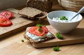 image of curd  - fresh curd cheese dip with herbs in a white bowl and rustic wholegrain bread with tomatoes on a kitchen board healthy and powerful meal with natural food products - JPG