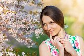 foto of orchard  - Beautiful young brunette woman in blooming orchard - JPG