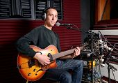 stock photo of singer  - a singer and his guitar in a recording studio - JPG