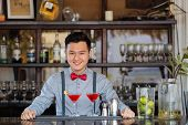 stock photo of bartender  - Smiling Asian bartender standing at the counter and looking at the camera - JPG