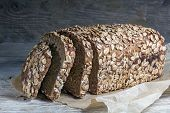 pic of whole-grain  - dark bread loaf with whole grain and seeds on an old wooden board - JPG