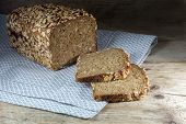 foto of whole-grain  - healthy bread loaf and slices with whole grain and seed on rustic wood dark background - JPG