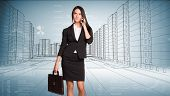 picture of up-skirt  - Businesswoman with suitcase talking on mobile phone looking up - JPG