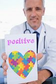 stock photo of prescription pad  - The word positive and portrait of a male doctor showing a blank prescription sheet against autism awareness heart - JPG