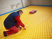 picture of convection  - group of workera installing underfloor heating and colling in modern home - JPG