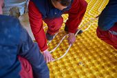 foto of convection  - group of workera installing underfloor heating and colling in modern home - JPG