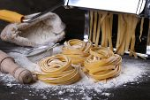 image of pasta  - Metal pasta maker machine and ingredients for pasta on wooden background - JPG