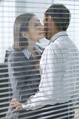 picture of office romance  - Businesswoman about to kiss businessman in office - JPG