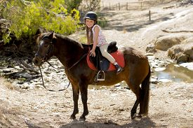 foto of year horse  - sweet beautiful young girl 7 or 8 years old riding pony horse and smiling happy wearing safety jockey helmet posing outdoors on countryside in summer holiday - JPG