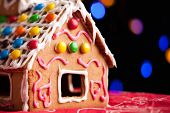 picture of gingerbread house  - Closeup of gingerbread house decorated with colorful candies over Christmas tree lights background - JPG
