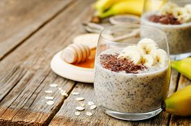 stock photo of oats  - overnight banana oats quinoa Chia seed pudding decorated with banana and chocolate - JPG