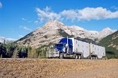 stock photo of 18-wheeler  - a semi truck going up through the canadian rockies with motion blur - JPG