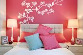 pic of mural  - Stylish brightly decorated modern bedroom with wall mural and cushions - JPG