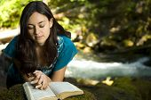 picture of humble  - Young woman reading bible by stream in summer - JPG