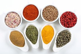 picture of flavor  - Flavorful colorful spices in ceramic bowls on white background - JPG
