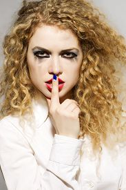picture of hush  - Portrait of one beautiful young blonde woman with curly hair and spooky eye makeup in white blouse with hush gesture standing in studio on light background vertical picture - JPG