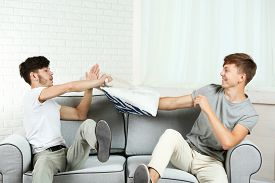 picture of pillow-fight  - Two brothers fighting with pillows on sofa at home - JPG