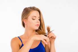 stock photo of split ends  - pretty woman cutting her split ends on a white background - JPG