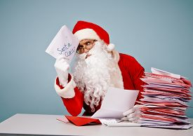 stock photo of letters to santa claus  - Pensive Santa Claus with Christmas letter sitting by table - JPG