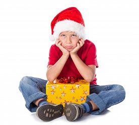 stock photo of sad christmas  - Sad boy with gift box in christmas hat - JPG