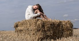 stock photo of haystacks  - Full length portrait of young adult girl on haystack against blue sky with clouds and autumn field wear white sweater - JPG