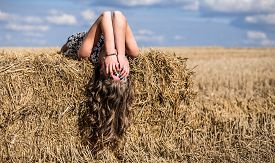 picture of haystacks  - Full length portrait of young adult girl on haystack against blue sky with clouds and autumn field wear white sweater - JPG